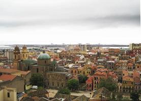 Cagliaris Skyline mit Gebäuden, Hafen, düsteren grauen Wolken foto