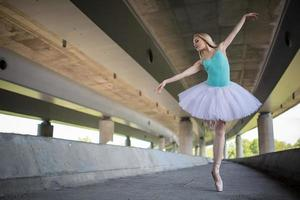 anmutige Ballerina, die Tanzübungen auf einer Betonbrücke macht foto