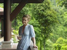 Frau auf der Veranda mit Glas Wasser foto