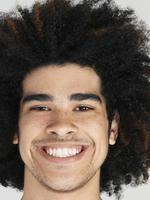 junger Mann mit Afro-Frisur lächelnd foto
