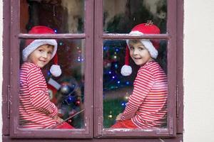 zwei süße Jungen, Brüder, die durch das Fenster schauen und auf den Weihnachtsmann warten