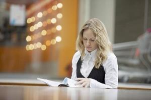 Geschäftsfrau liest Magazin am Foodcourt foto