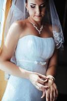 schöne Braut, die im weißen Hochzeitskleid mit Frisur fertig wird foto