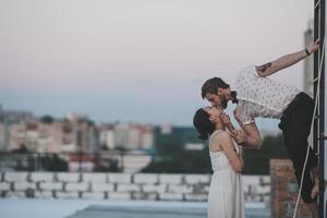 Mann lehnt sich aus dem Fenster, um Frau im Stadtbild zu küssen foto