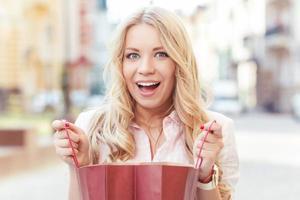 blondes Mädchen, das Spaß nach dem Einkaufen hat foto