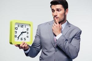 nachdenklicher Geschäftsmann, der Uhr hält foto