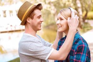 hübscher Mann, der Kopfhörer auf hübsches Mädchen setzt foto