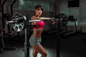 schönes Sport-Fitness-Mädchen mit einer Langhantel foto