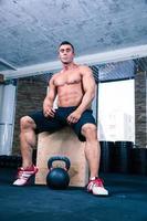 muskulöser Mann, der auf fit box im Fitnessstudio sitzt foto