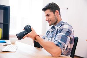glücklicher Mann, der am Tisch mit Fotokamera sitzt foto