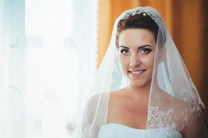 schöne Braut, die sich im weißen Hochzeitskleid mit Frisur fertig macht foto