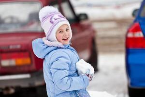 das Mädchen mit einem Schneeball in den Händen foto