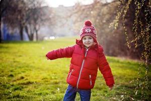 lustiger kleiner Junge, der sonnigen Frühlingstag im Park genießt foto