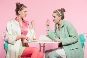 zwei Mädchen blonde Haare fünfziger Jahre Modestil essen Eis.