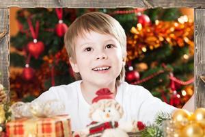 Junge hält Holzrahmen foto
