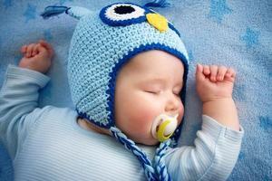 Baby im Eulenhut schläft