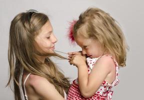 junges Mädchen hält ihre kleine Schwester in den Armen.