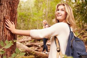 Mädchen, das einen Baum im Wald berührt foto