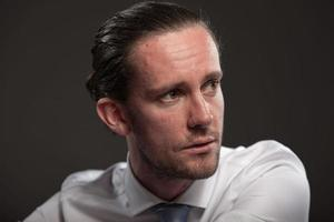 Mann braunes Haar, das Hemd und Krawatte trägt Emotionen zeigt.
