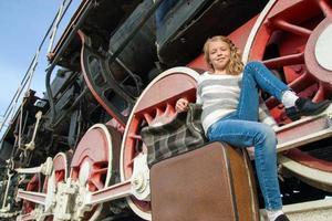 Mädchen warten auf die Landung auf dem Bahnsteig im Vintage-Zug foto
