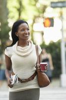 Frau mit Zeitung und Kaffeetasse auf der Straße