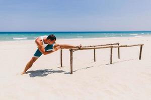 Mann streckt sich am Strand foto