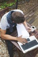 junger Mann, der mit Laptop im Freien arbeitet.