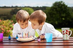 entzückende Jungen, die Kerzen auf einer Geburtstagstorte blasen foto