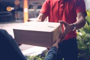 Lieferbote gibt Paket an Kunden foto