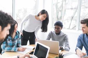 junge Berufstätige, die in einem Büro an Laptops arbeiten foto