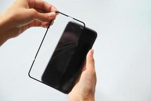 Nahaufnahme der Person, die rissige Smartphone-Abdeckung repariert foto