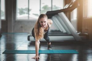 Frau macht Einhand-Liegestütz im Fitnessstudio