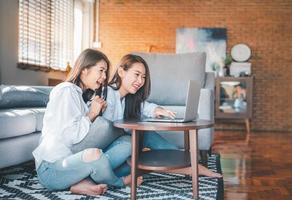 zwei asiatische Frauen lachen, während sie mit Laptop zu Hause arbeiten