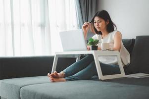Frau denkt, während sie zu Hause auf dem Sofa arbeitet