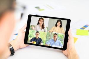 Geschäftsmann trifft sich mit asiatischen Kollegen in Videokonferenz foto