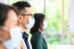 Gruppe von asiatischen Menschen, die aus Sicherheitsgründen Gesichtsmasken tragen