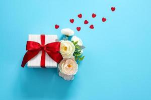 Geschenkbox mit Blumen und Herzen auf blauem Hintergrund foto