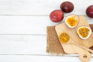 frische Passionsfrüchte auf weißem Holztisch mit Schneidebrett foto