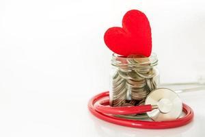 Stethoskop um ein Glas Münzen mit Herz gewickelt foto