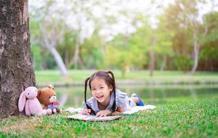 junges Mädchen im Park mit Buch und Puppen