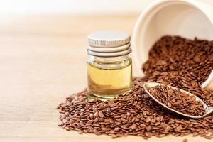 Nahaufnahme von Leinsamen und Leinsamenöl auf Holztisch