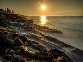 Langzeitbelichtung von Meereswellen am felsigen Strand foto