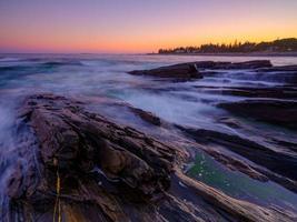 Langzeitbelichtung von Wellen auf Felsen foto