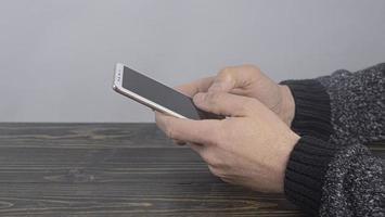 Mann sitzt am Tisch und hält Telefon