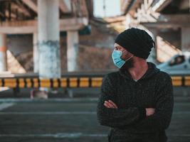 Mann trägt draußen eine medizinische Maske foto