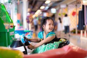 kleines asiatisches Mädchen reitet auf Spielzeugauto im Einkaufszentrum