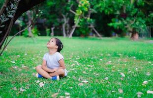 süßes asiatisches kleines Mädchen, das im Park sitzt und aufschaut
