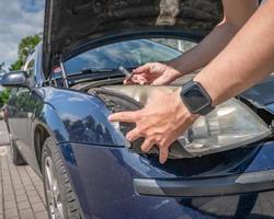 Autobesitzer wechselt Frontscheinwerfer foto