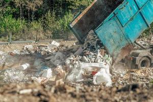 LKW, der gemischten Abfall auf Deponie deponiert foto