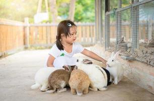 junges Mädchen, das Kaninchen auf der Farm füttert foto